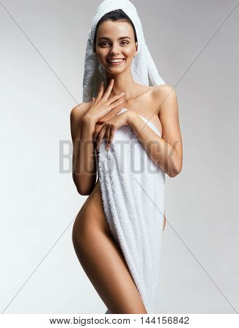 Sexy young woman in towel. Photo of smiling girl with perfect body. Wellness and Spa concept