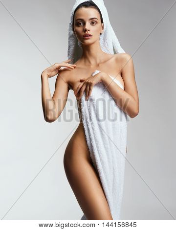 Beautiful sexy female touching her perfect skin. Photo of woman in towel show her tan slim body. Beauty & Skin care concept