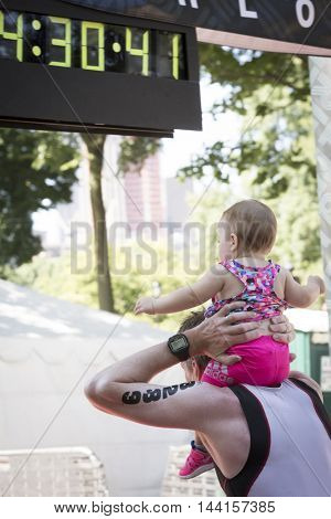 NEW YORK JUL 24 2016: A man with a baby on his shoulders crosses the finish line of the NYC Triathlon Race in Central Park. The run is 10k and is the only International Distance triathlon in the city.