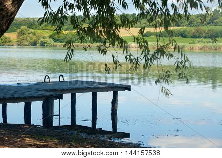 Tranquil lake water under the old wooden pontoon