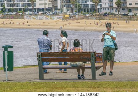MONTEVIDEO, URUGUAY, DECEMBER - 2015 - Group of people at park in front of beach in Montevideo Uruguay