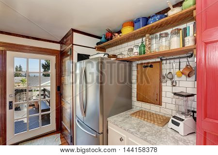 Old Style Kitchen Interior. Wooden Shelves And Steel Fridge