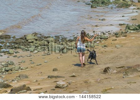 Young woman playing with a black dog at shore at beach in Montevideo Uruguay