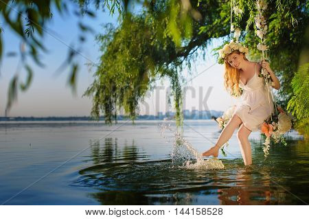Girl on home made tree swing over river. Swing decorated with flowers. Smiling girl sitting on swing. Girl with flower wreath on head.