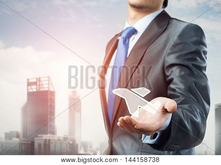 Close up of businessman hand holding airplane icon in palm