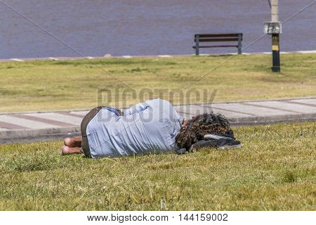 Back view of indigent sleeping at grass in Park