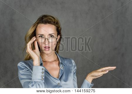 Beautiful girl smiles and looks in surprise and raises his hand on a gray background