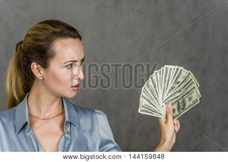 Beautiful girl smiling and looking up and holding in his hand the money over gray background