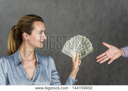 Beautiful girl holding money and a man's hand picks up, action on a gray background