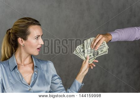 Beautiful girl holding a money and a man's hand picks up, action on a gray background