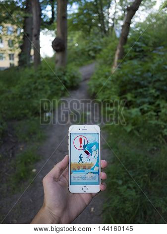 Gothenburg, Sweden - July 26, 2016: Teenaged man holding a smartphone while playing Pokemon Go, a free-to-play location based augmented reality mobile game developed by Niantic for iOS and Android devices.