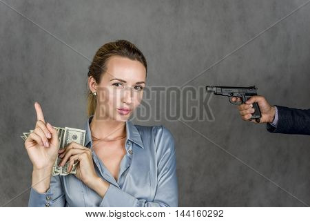 Girl with money and hand with gun