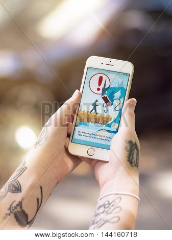 Gothenburg, Sweden - July 28, 2016: Tattooed woman holding a smartphone while playing Pokemon Go, a free-to-play location based augmented reality mobile game developed by Niantic for iOS and Android devices.
