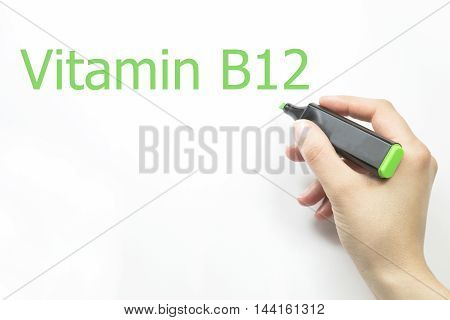 Hand writing vitamin b12 with green marker on transparent wipe board