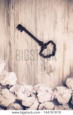 Vintage key among many balls of crumpled paper