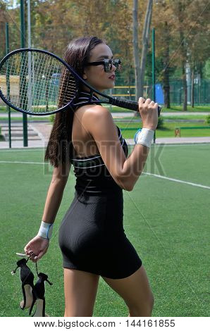 Girl Is On The Court With A Racket On Her Shoulder.