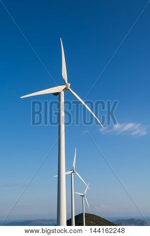 Three white wind turbines against blue sky