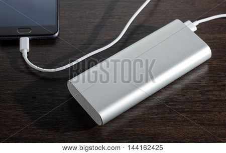 Smartphone charged by power bank - dark wooden background