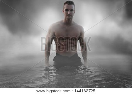 Sexy male standing in the water over a cloudy sky