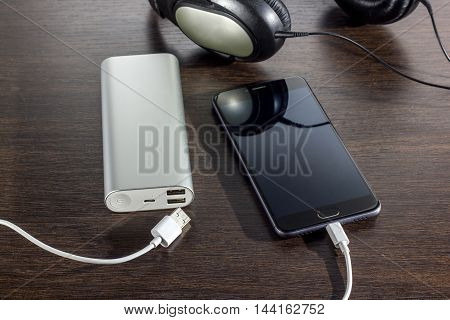mobile phone and power bank battery on dark wooden background