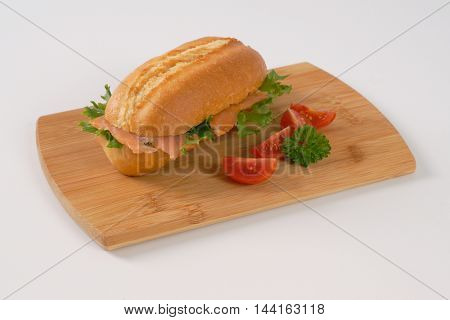 sandwich with smoked salmon on wooden cutting board