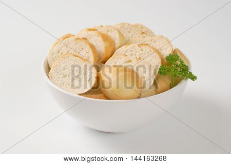 bowl of sliced french baguette on white background
