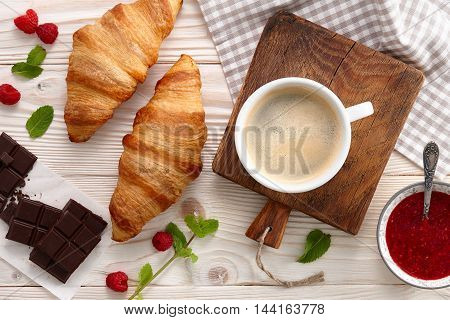 Morning breakfast with americano coffee, raspberry jam and fresh croissants.