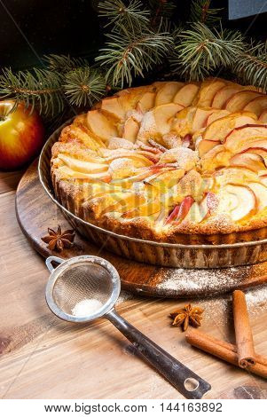 Traditional apple pie on a wooden table, with apple and powdered sugar. Near the Christmas tree branches