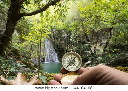Man's hand holding a compass in the forest concept of seeking exploration achievement. Selective focus