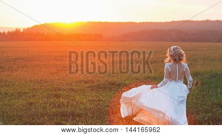 beautiful bride in a field at sunset.