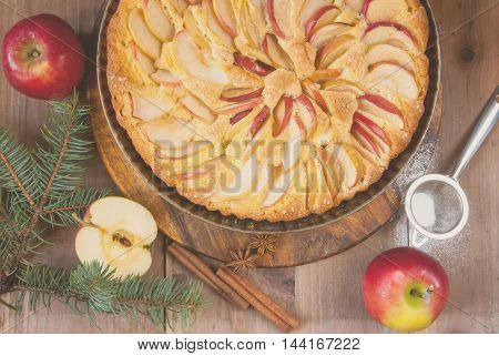 Traditional apple pie on a wooden table, with apple and powdered sugar. Near the Christmas tree branches and spices, top view, toned