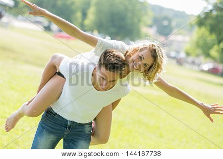 Man giving piggyback ride- carrying on the back his girlfriend