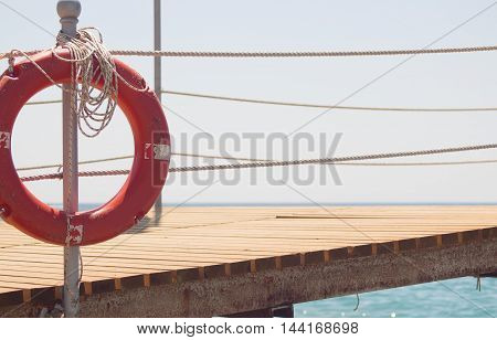 Red lifebuoy on pier. Round red equipment placed on pier. Lifeguard safety circle