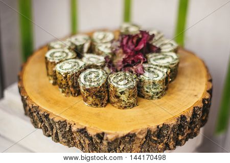 Roll with spinach sliced on wooden stump
