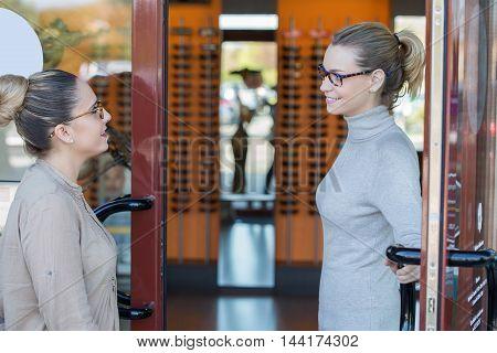woman Optician opening door to the patient