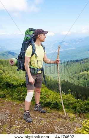 Young hiker with bandage on knee and cane in hand in mountains. Male wearing shorts on top of mountain with wrapped injured knee with white sports bandage. Hiking