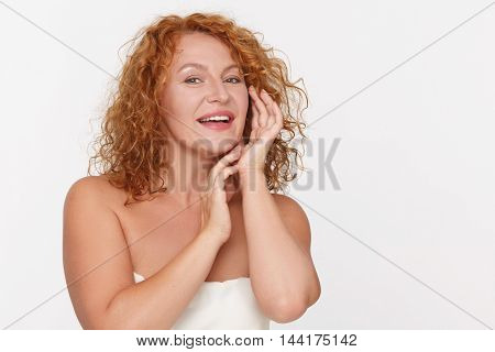 Portrait of beautiful mature ormiddle aged woman, aged 40, looking after her skin isolated on white background in studio. Skincare concept.
