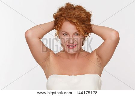 Portrait of beautiful mature of middle aged woman looking after her hair isolated on white. Pretty senior lady looking at camera in studio.