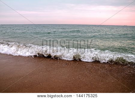 Warm autumn evening on the shore of the Black Sea with waves