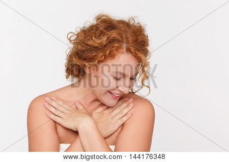 Beautiful red haired woman smiling for camera isolated on white. Pretty middle aged lady looking down in studio. Emotions concept.
