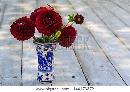 Home garden burgundy dahlias in a delft pottery vase under dappled shade.