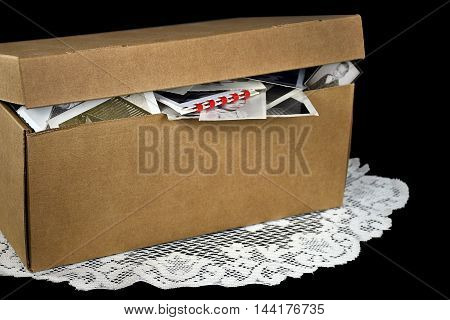 Old family photos in generic brown cardboard box on lace doily