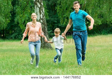 Happy Family Holding Each Other Hands While Running In The Park