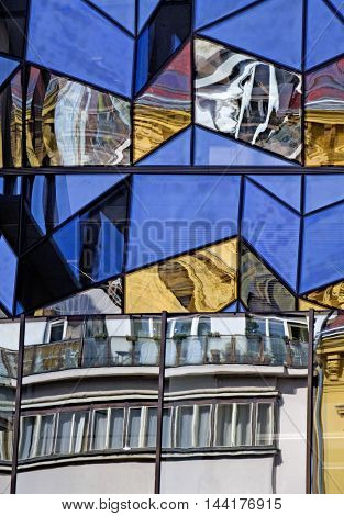 reflections of an old historic building in the glass walls of a modern building in prague
