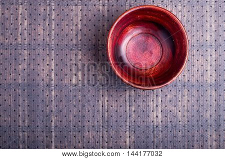 The surface of the table with a brown wooden bowl on a background of the fabric
