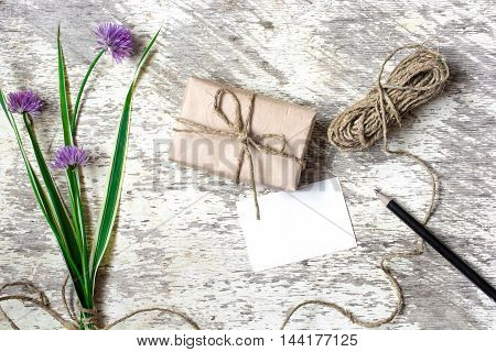 vintage gift box with blank white greeting card and purple flowers and rope over white wooden background