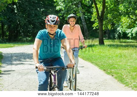 Young Smiling Couple Enjoying The Ride On Bicycle In The Park