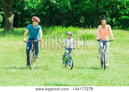 Happy Boy With His Parent Riding Bicycle In The Park