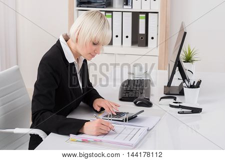 Young Female Accountant Working With Calculator In Office