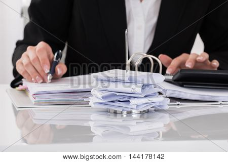 Close-up Of Female Accountant Calculating Tax At Desk